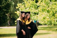 Riga, Latvia Dois graduados das jovens mulheres da universidade de Letónia vestiram-se em graduados do vestido e em tampões acadê Foto de Stock