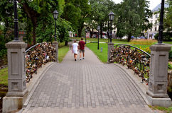 RIGA / LATVIA - July 27, 2013: Couple walk in the city park near the bridge with many padlocks as a signs of love. RIGA / LATVIA - July 27, 2013: Couple (man and Stock Photo