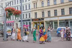 Group of the Hare Krishna people walking and singing in the streets of Riga royalty free stock photos