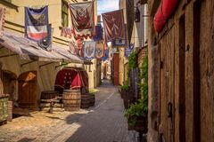 Riga, Latvia - July, 2013. Medieval street and fragment of outdoors cafe in the old city of Riga. Medieval street and fragment of outdoors cafe in the old city royalty free stock image