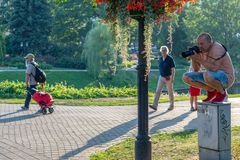 RIGA, LATVIA - JULY 26, 2018: The photographer ascended up to the electric cabinet in a city park stock photos