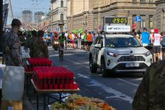Riga, Latvia - May 19 2019: First Elite runners approaching refreshment station behind chase car royalty free stock image