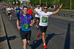 Riga, Latvia - May 19 2019: Happy caucasian mare marathon runners hands up with sunglasses royalty free stock photography