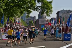 Riga, Latvia - May 19 2019: Marathon runners reaching freedom statue with traditionally clothed cheerleaders are giving high fives royalty free stock photo
