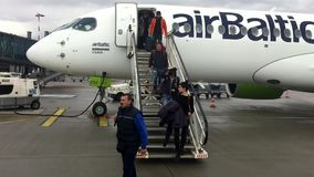 Passengers get off the Airbaltic plane arrived in Riga on a rainy day. stock footage