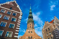 RIGA, LATVIA - MAY 06, 2017: View on Riga`s St.Peter`s Church, restaurants, cafe and nearest houses are located in th. E city center of Riga stock photography