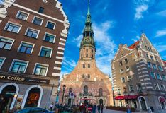 RIGA, LATVIA - MAY 06, 2017: View on Riga`s St.Peter`s Church, restaurants, cafe and nearest houses are located in th. E city center of Riga royalty free stock images