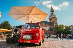 Riga, Latvia O carro vermelho grande de suportes dos Buskers dos músicos da rua aproxima o café Fotografia de Stock Royalty Free