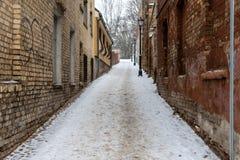 riga latvia Paisagem do inverno com o trajeto pedestre entre casas velhas do tijolo foto de stock royalty free