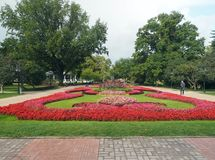 Editorial Vermanes Garden park by National Opera Riga Latvia. RIGA, LATVIA-SEPT. 27:  Vermanes Garden park with grass, flowers and tourists is seen by National Royalty Free Stock Image