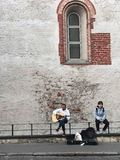 Riga, Latvia, September 18, 2018. One guy plays the guitar and sings a romantic song, the second one listens. Near the case from royalty free stock photos