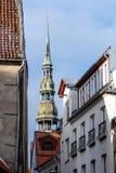 riga latvia A torre de St Peters Church pode ser vista entre casas velhas de Riga imagem de stock