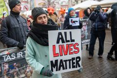 Young woman keeping sign - All lives matter in her hands, during `March for animals` in Riga, Latvia. 24.11.2018. RIGA, LATVIA. Young woman keeping sign - All stock photography