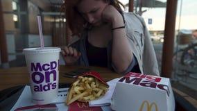 RIGA, LETÓNIA - 22 DE ABRIL DE 2019: Jovem mulher que usa seu iPhone ao comer no restaurante Mcdonalds do fast food - Big Mac filme