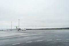 RIGA, LETÓNIA - 24 DE JANEIRO DE 2017: Aeroporto internacional de Riga com o traço Báltico 8 Q400 do bombardeiro do avião do ar n Fotos de Stock