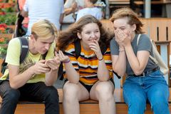RIGA, LETÓNIA - 26 DE JULHO DE 2018: Os adolescentes sentam-se no banco, falam-se e riem-se foto de stock royalty free