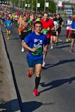 Riga, Let?nia - 19 de maio de 2019: Corredor de maratona novo com os fones de ouvido com a multid?o grande no fundo imagens de stock royalty free