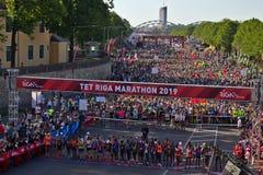 Riga, Let?nia - 19 de maio de 2019: Corredores da elite da maratona de Riga TET que enfileiram no in?cio a linha etnicamente dive fotos de stock