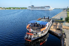 Riga, Letónia - 21 de maio de 2016: Navio de cruzeiros CAM Opera que gira circularmente e barco de rio turístico com a roda de pá Imagens de Stock