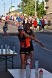 Riga, Let?nia - 19 de maio de 2019: Os esportes de agarramento do corredor f?mea caucasiano da elite bebem com velocidade grande imagem de stock royalty free