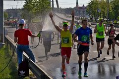 Riga, Let?nia - 19 de maio de 2019: Participante masculino da maratona feliz correr embora o pulverizador de ?gua imagem de stock