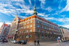RIGA, LETÓNIA - 6 DE MAIO DE 2017: A vista na igreja do ` s do ` s StPeter de Riga, os restaurantes, o café e as casas as mais pr imagem de stock