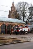 RIGA, LETÓNIA - 16 DE MARÇO DE 2019: O carro de bombeiros está sendo - o motorista lava o caminhão do sapador-bombeiro em um depo imagem de stock