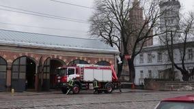 RIGA, LETÓNIA - 16 DE MARÇO DE 2019: O carro de bombeiros está sendo - o motorista lava o caminhão do sapador-bombeiro em um depo video estoque