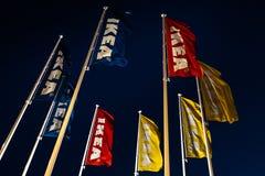 Riga, Let?nia - 3 de abril de 2019: Bandeiras de IKEA durante a noite escura e vento - c?u azul no fundo fotografia de stock royalty free