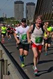 Riga, Let?nia - 19 de maio de 2019: Corredor de maratona idoso que cruza bravamente uma ponte fotos de stock royalty free