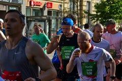 Riga, Let?nia - 19 de maio de 2019: ?gua pot?vel dos corredores de maratona na multid?o grande imagem de stock royalty free