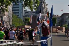 Riga, Let?nia - 19 de maio de 2019: Os corredores de maratona que alcan?am a est?tua da liberdade com os l?der da claque tradicio fotos de stock