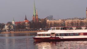 RIGA, LETLAND - APRIL 7, 2019: Boot Vecriga die langs de rivier Daugava met mening over Oude Stad op de achtergrond varen - stock video