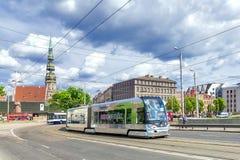 RIGA, 10 LETLAND-JUNI, 2017: een moderne tram in de oude straten van Riga Tegen de achtergrond van de Kathedraal van Perth royalty-vrije stock foto's
