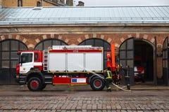 RIGA, LETLAND - MAART 16, 2019: De brandvrachtwagen wordt schoongemaakt - de brandbestrijdersvrachtwagen van Bestuurderswassen bi royalty-vrije stock foto's