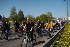 RIGA, LETLAND - MEI 1, 2019: Fietsparade op Arbeidsdag met families en vrienden op openbare ruimteweg met andere auto's stock foto