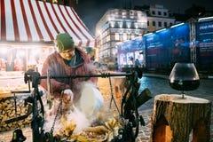 Riga, Letland Mensen bradend varkensvlees - een traditionele Kerstmisschotel van straatvoedsel op straten van Europa in de winter royalty-vrije stock foto