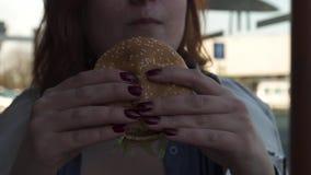 RIGA, LETONIA - 22 DE ABRIL DE 2019: Cierre de la hamburguesa encima - mujer joven que come en el restaurante Mcdonalds de los al metrajes