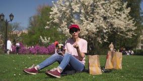 RIGA, LETONIA - 28 DE ABRIL DE 2019: Mujer de negocios acertada que come el cheesburger de la hamburguesa del Big Mac de McDonald metrajes