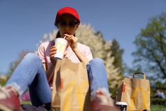 RIGA, LETONIA - 28 DE ABRIL DE 2019: Mujer de negocios acertada que come el cheesburger de la hamburguesa del Big Mac de McDonald imagen de archivo