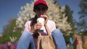 RIGA, LETONIA - 28 DE ABRIL DE 2019: Mujer de negocios acertada que come el cheesburger de la hamburguesa del Big Mac de McDonald almacen de metraje de vídeo