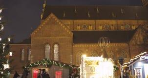 Riga, Letonia - 18 de diciembre de 2017: Gente que camina cerca de mercado tradicional de la Navidad en cuadrado de la bóveda con almacen de video