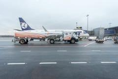RIGA, LETONIA - 24 DE ENERO DE 2017: Aeropuerto internacional de Riga con el camión del depósito del aeroplano y de gasolina de P Imágenes de archivo libres de regalías