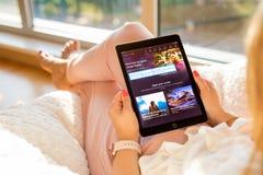 Riga, Letonia - 21 de julio de 2018: Mujer que mira página web barata de la búsqueda del vuelo de Momondo en iPad foto de archivo libre de regalías