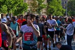 Riga, Letonia - 19 de mayo de 2019: Agua potable del hombre joven del corredor de marat?n imágenes de archivo libres de regalías