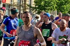 Riga, Letonia - 19 de mayo de 2019: Agua potable de los corredores de marat?n en muchedumbre grande imagen de archivo