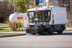 Riga, Letonia - 5 de mayo de 2017: Vehículo del barrendero que barre la calle Imágenes de archivo libres de regalías