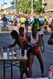 Riga, Letonia - 19 de mayo de 2019: Tres corredores femeninos de la ?lite que encuentran sus deportes beben de la tabla durante m fotografía de archivo libre de regalías
