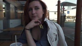 RIGA LETTLAND - APRIL 22, 2019: Framsidaslut upp - den unga kvinnan som äter i snabbmatrestaurangen Mcdonalds - Big Mac, medel lager videofilmer