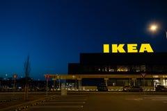 RIGA LETTLAND - APRIL 3, 2019: IKEA m?rkestecken under m?rk afton och vind - bl? himmel i bakgrunden royaltyfria bilder